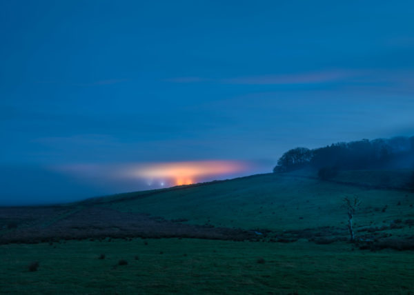 The lights from dartmoor prison glowing in the early evening mist